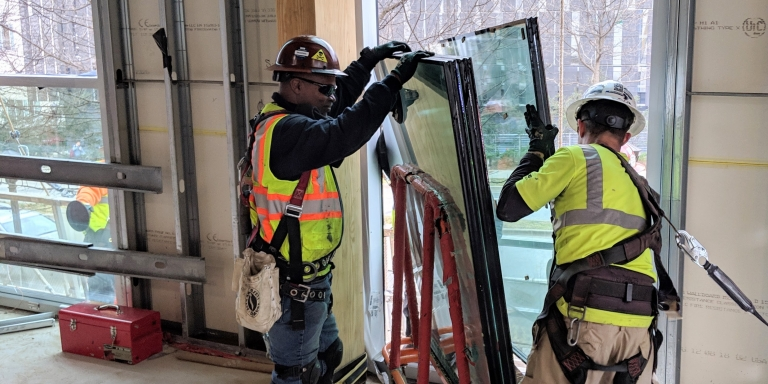Installation of triple pane windows. Both half-inch spaces between the three quarter-inch panes are filled with argon gas, which has greater insulating qualities than air.